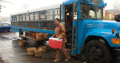 A man emerges from the bus carrying a cooler.